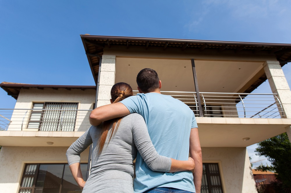 couple hugging each other in front of new house