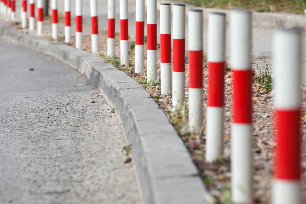 Striped red and white signal poles stand on border of asphalt roadside