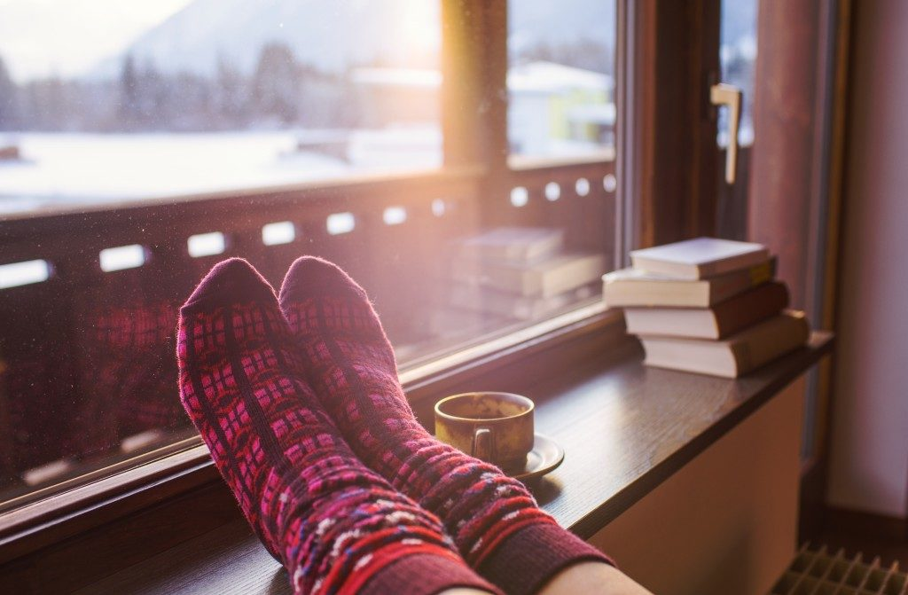 Feet in woollen socks and a cup of hot drink
