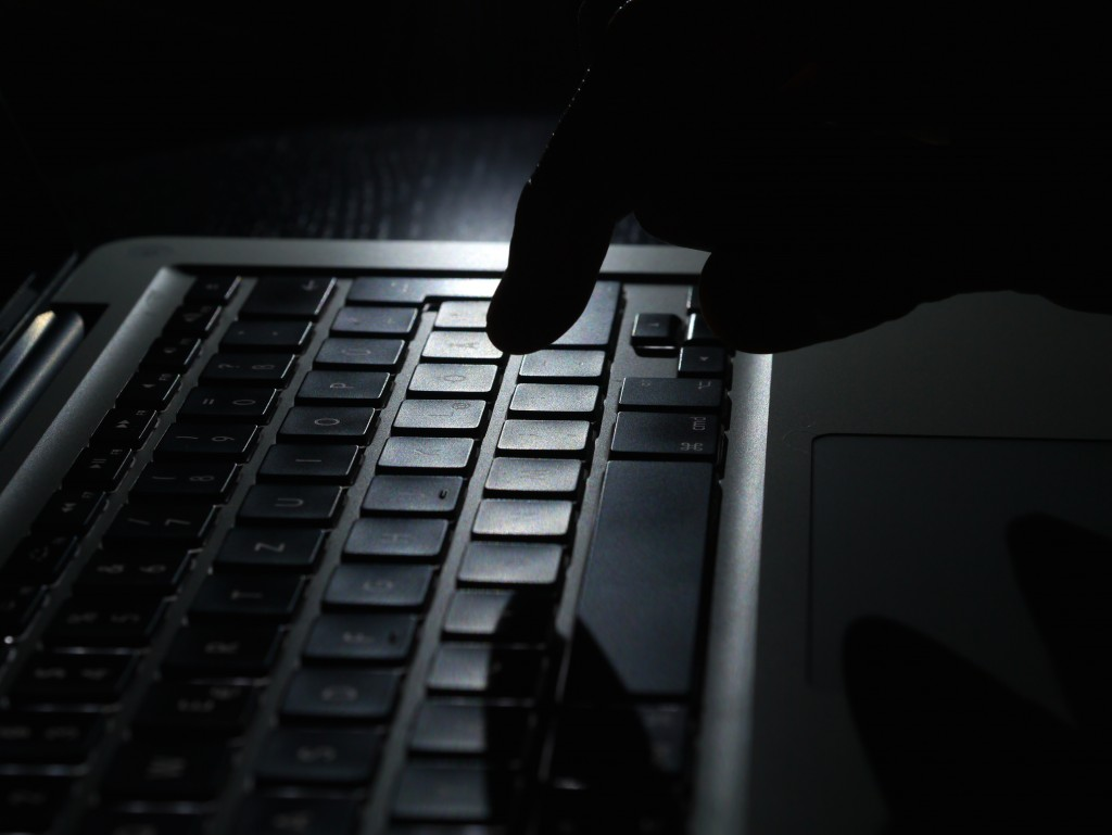 Cybercrime - one finger shadow on keyboard