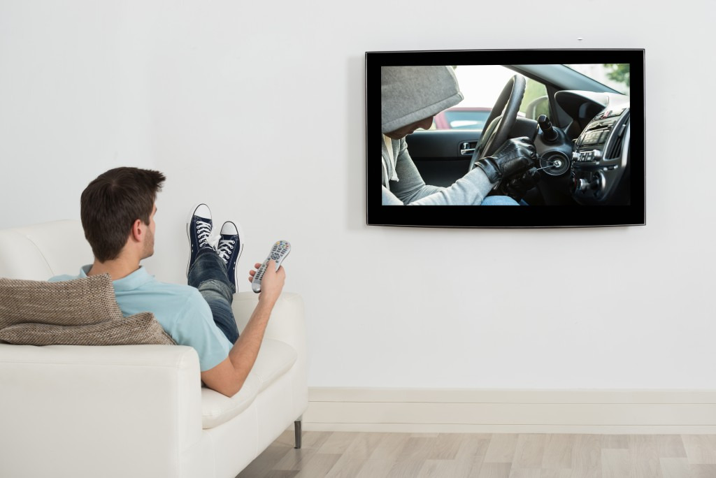 Young Man Lying On Couch Watching Movie On Television