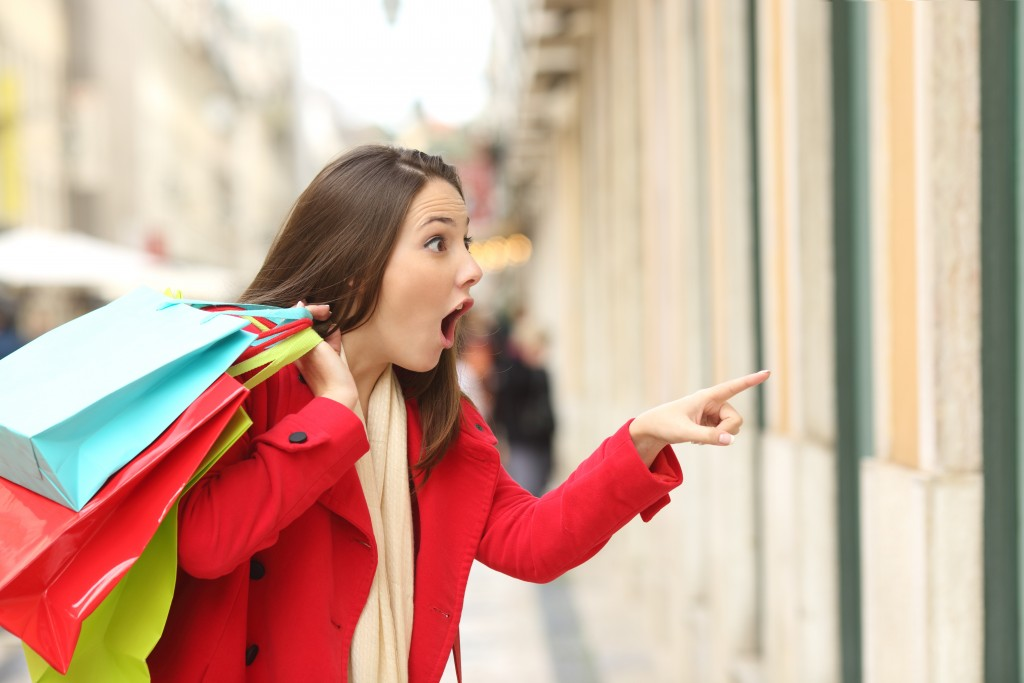 Amazed shopper opening mouth holding shopping bags