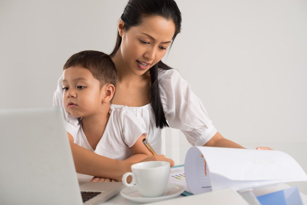 mom studying while taking care of her son