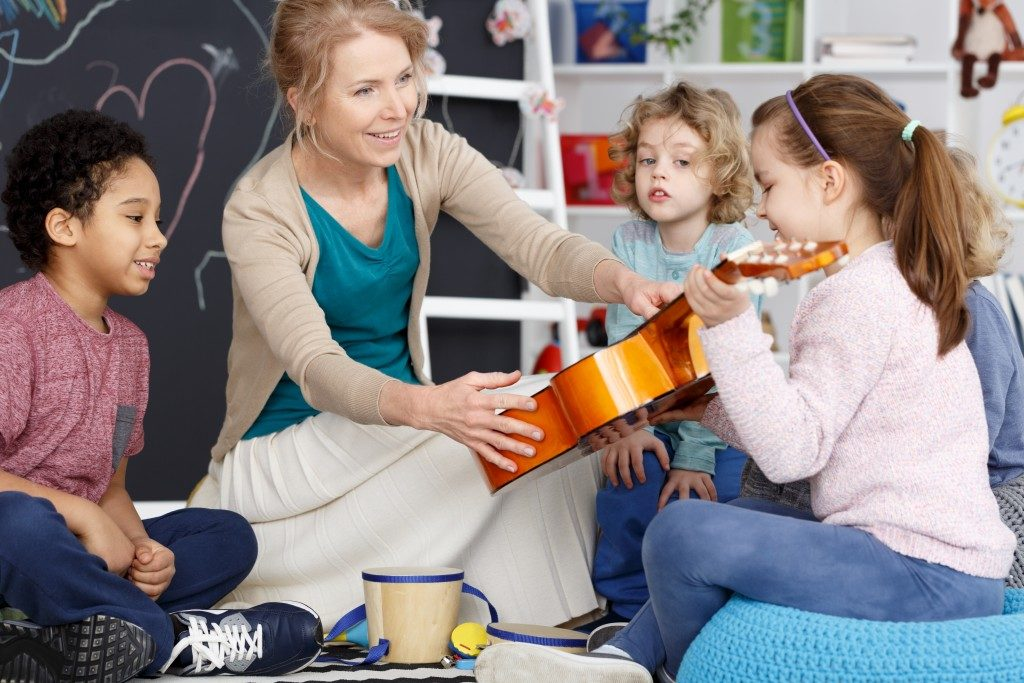 teacher teaching her students how to play a guitar
