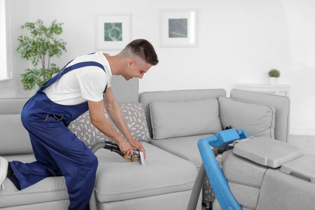 Man vacuuming the couch