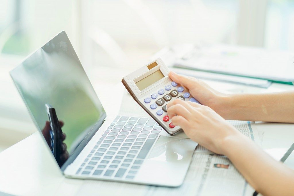 close up shot of woman's hands holding a calculator in front of a laptop