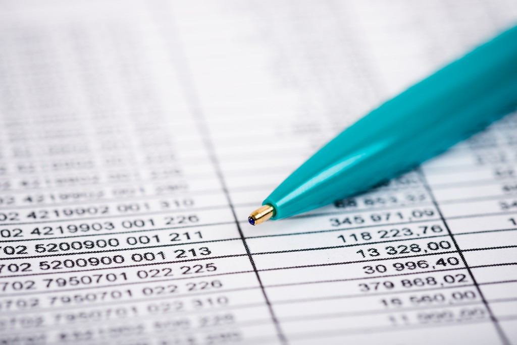 close up shot of an accounting sheet with a blue ballpen on top