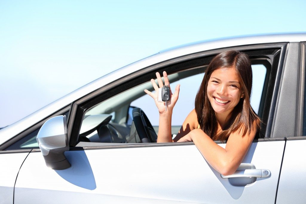 Woman holding car keys while in car