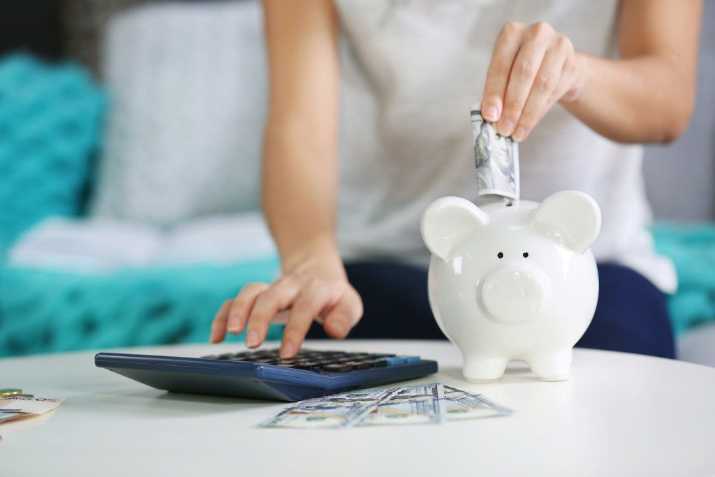 woman inserting money on a piggy bank