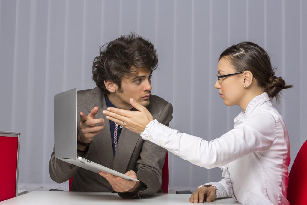 Man showing laptop to female