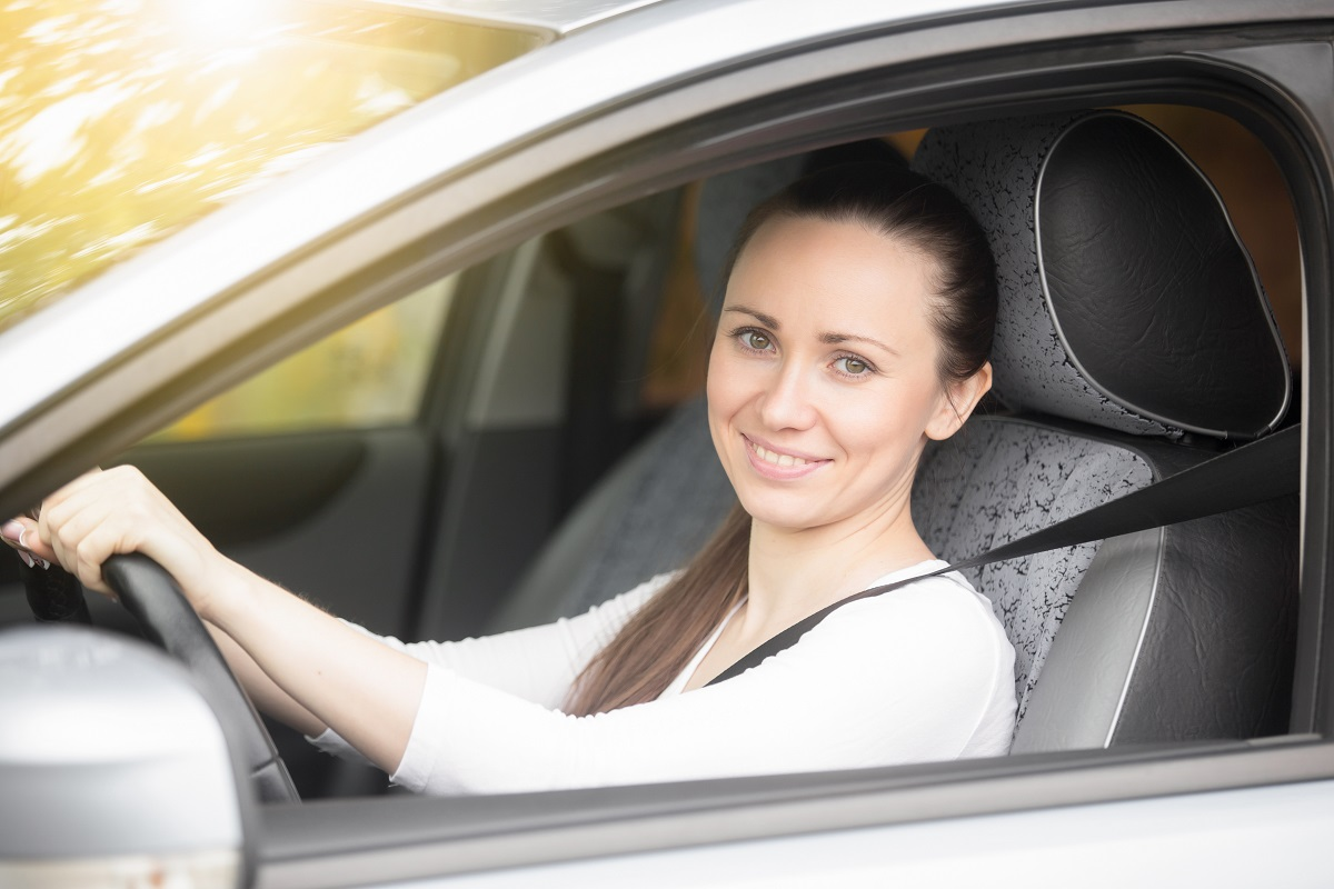 Portrait of smiling lady driver showing thumb up