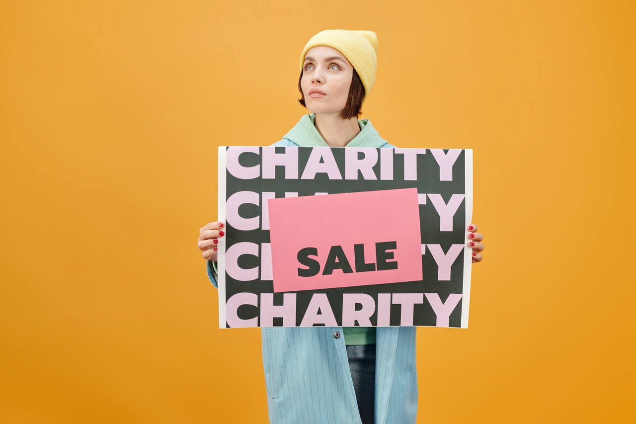 woman holding sign charity sale