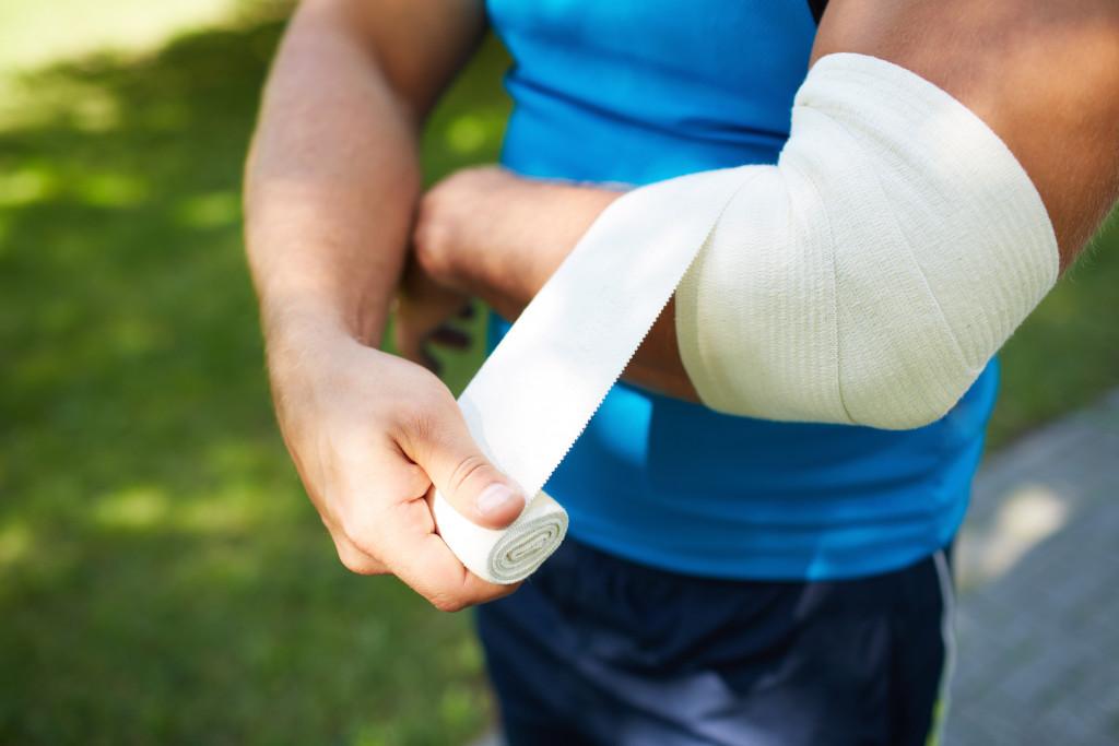 man wrapping elbow injury